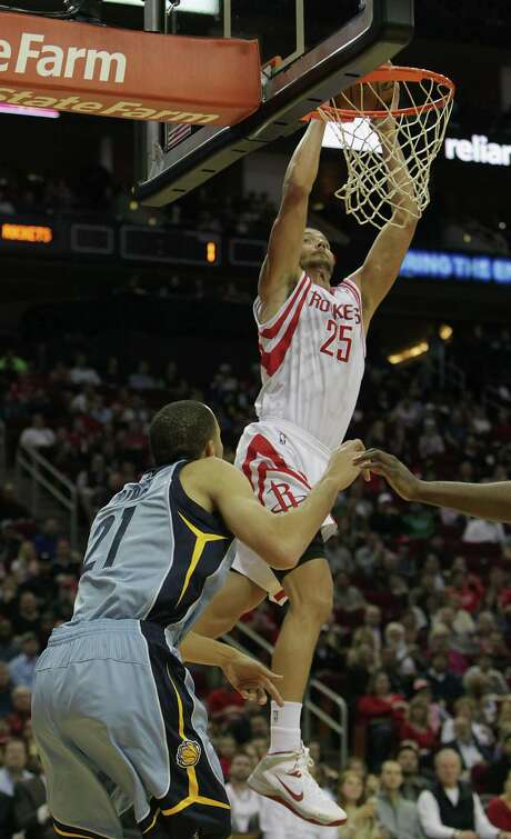 The Rockets' Chandler Parsons dunks over the Grizzlies' Tayshaun Prince on Thursday night. Photo: James Nielsen, Staff / © 2013  Houston Chronicle