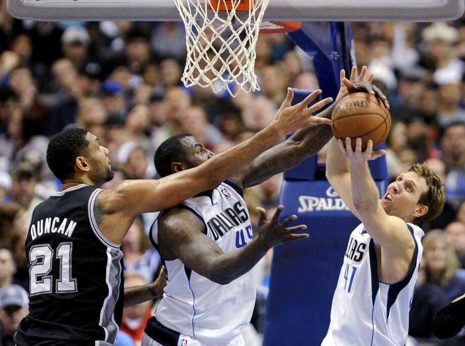 San Antonio Spurs forward Tim Duncan (21) and Dallas Mavericks center DeJuan Blair and forward Dirk Nowitzki (41) go after a rebound during the second half of an NBA basketball game, Thursday, Dec. 26, 2013, in Dallas. The Spurs won 116-107. Photo: Matt Strasen, Associated Press