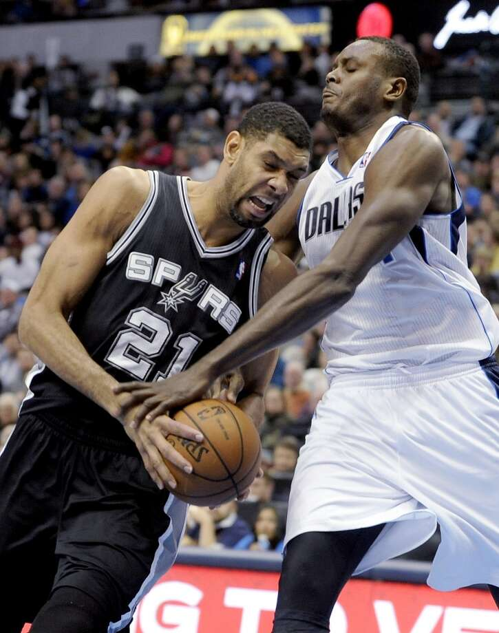 San Antonio Spurs forward Tim Duncan (21) is fouled by Dallas Mavericks center Samuel Dalembert during the second half during an NBA basketball game, Thursday, Dec. 26, 2013, in Dallas. The Spurs won 116-107. Photo: Matt Strasen, Associated Press