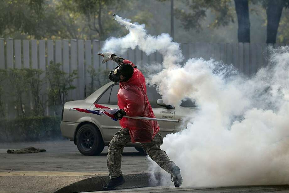A Thai anti-government protester throws back tear gas canister at riot policemen during a clash at a sport stadium in Bangkok, Thailand Thursday, Dec. 26, 2013. Rock-throwing protesters trying to halt preparations for elections fought police in the Thai capital on Thursday, escalating their campaign to topple the country's beleaguered government. (AP Photo/Wason Wanichakorn) Photo: Wason Wanichakorn, Associated Press