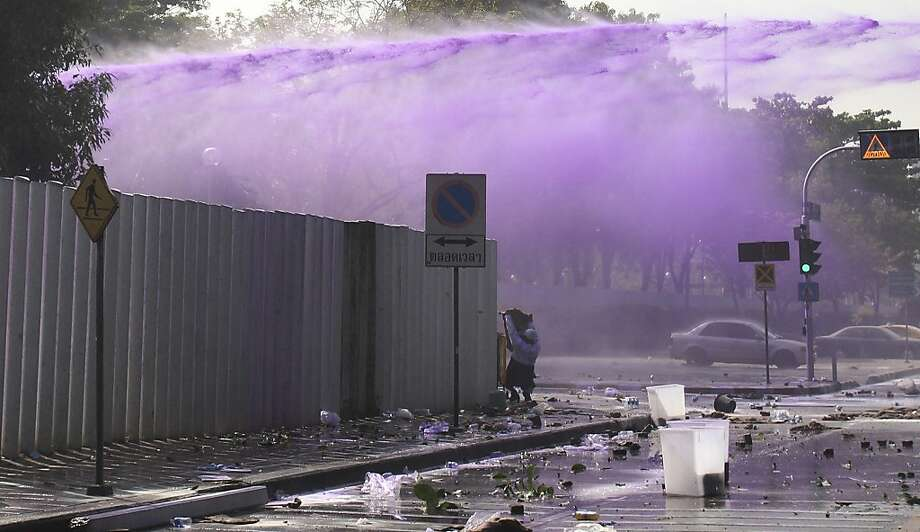 A man shield himself as riot police shoots water cannon at anti-government protesters at a gymnasium in Bangkok, Thursday, Dec. 26, 2013. Protesters trying to halt preparations for elections fought running battles with police in the Thai capital on Thursday, escalating their campaign to topple the country's beleaguered government. (AP Photo/Sakchai Lalit) Photo: Sakchai Lalit, Associated Press