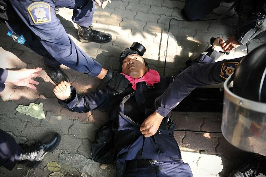 BANGKOK, THAILAND - DECEMBER 26: A policeman lies injured from a gunshot wound to the chest after police come under fire at a sports stadium where the Thai Election Commission is registering candidates for Thailand's upcoming poll on December 26, 2013 in Bangkok, Thailand. The policeman later died of his injuries. Several thousand anti-government protesters clashed with police guarding the election registration venue. Police used tear gas, rubber bullets and waters canons, while gunfire was heard on several occasions from both sides of the police line. Protesters demand that the election be called off and an appointed government takes power until political reforms have taken place. (Photo by Rufus Cox/Getty Images) *** BESTPIX *** Photo: Rufus Cox, Getty Images