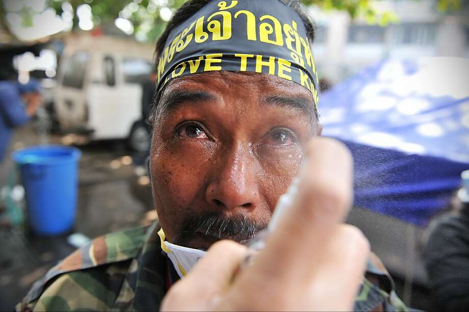 BANGKOK, THAILAND - DECEMBER 26: An anti-government protesters overcome by tear gas has his eyes rinsed with saline during a violent protest at a sports stadium where the Thai Election Commission is registering candidates for Thailand's upcoming poll on December 26, 2013 in Bangkok, Thailand. Several thousand anti-government protesters fought with police guarding the election registration venue. Police used tear gas, rubber bullets and waters canons, while gunfire was heard on several occasions from both sides of the police line. One policeman died of a gunshot wound, while nearly one hundred people were injured during the clashes, including protesters, police and media. Protesters demand that the election be called off and an appointed government takes power until political reforms have taken place. (Photo by Rufus Cox/Getty Images) *** BESTPIX *** Photo: Rufus Cox, Getty Images