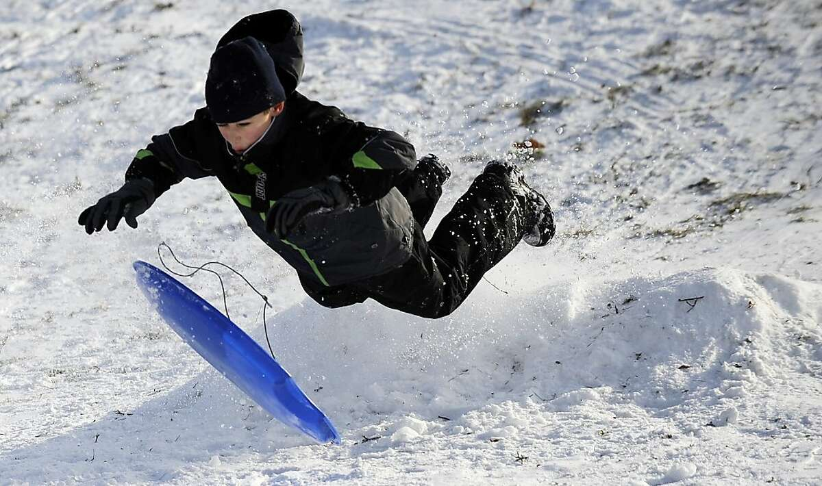 Evan Straske, 11, of Huntington Woods, Mich., takes flight after hitting a mound while sledding down a hill at Martin Road Park in Ferndale, Mich., on Thursday, Dec. 26, 2013. Children and adults took advantage of Thursday's fresh powder and no school to enjoy the winter break. (AP Photo/Detroit News, Elizabeth Conley)