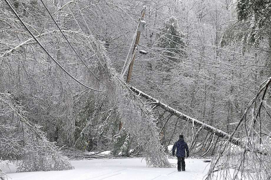 Karen Gibbs walks through a labyrinth of icy broken trees and downed power lines to her home on Maplehurst Drive in Belgrade, Maine on Thursday, Dec. 26, 2013. Southeast Maine and parts of the state's interior that have been without electricity since Sunday anticipated 3 to 7 inches of snow by the time the latest system pushed off the coast Thursday night. Utilities worried that the additional weight on branches and transmission lines could cause setbacks in the around-the-clock efforts to restore power. (AP Photo/The Central Maine Morning Sentinel, Michael G. Seamans) Photo: Michael G Seamans, Associated Press