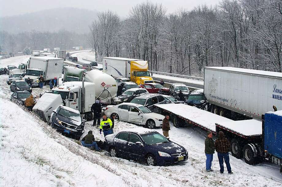 Vehicles are piled up at mile marker 286 on the Pennsylvania Turnpike, a mile outside Reading, Pa., on Thursday, Dec. 26, 2013. Portions of both the Pennsylvania Turnpike and Interstate 78 were shut down in snowy eastern Pennsylvania Thursday after chain-reaction pileups involved dozens of vehicles on slippery roads. (AP Photo/David C. Ronk) Photo: David C. Ronk, Associated Press