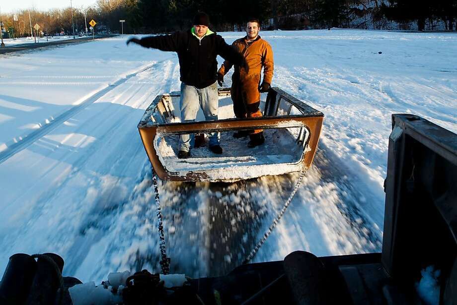 Bryston Embrey, left, 20, and Zachary Gray, 20, are pulled on an old truck cap chained to a pickup truck driven by Tessa Burley in St. Joseph, Mo., Thursday, Dec. 26, 2013. The friends enjoyed the snow as the weather warmed. (AP Photo/The St. Joseph News-Press, Sait Serkan Gurbuz) Photo: Sait Serkan Gurbuz, Associated Press