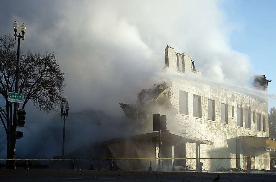 Firefighters hose down what remains of the vacant three-story Porterville Hotel Thursday, Dec. 26, 2013, after a fire destroyed the building in Porterville, Calif. (AP Photo/The Porterville Recorder, Chieko Hara) Photo: Chieko Hara, Associated Press