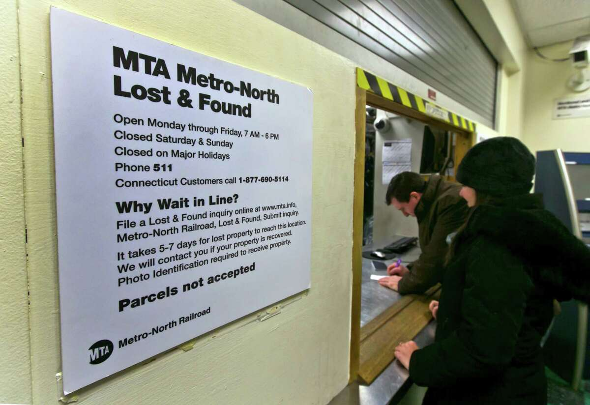 In this Tuesday, Dec. 17, 2013 photo, a couple retrieves a lost item at the window of the MTA Metro-North Lost and Found department, at New York's Grand Central Terminal. Officials in charge of the lost-and-founds say the holiday season is the busiest of the year.