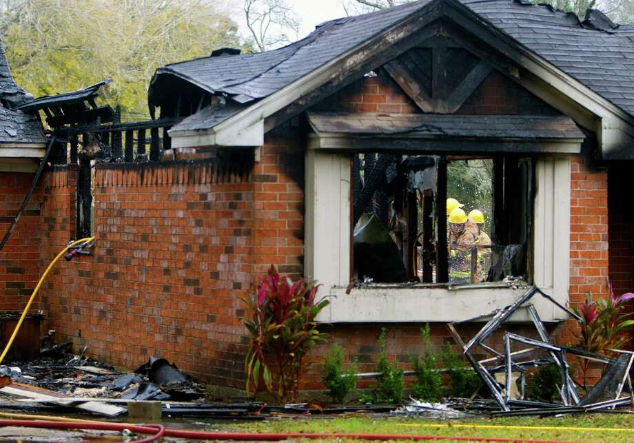 Firefighters work the scene after a blaze tore through a home in the 6700 block of Meadowlark Drive, Friday, Dec. 27, 2013, in Alvin. Liverpool, Danbury and Alvin responded to the blaze that started at around 7:30 a.m., and are still investigating how it started. Occupants were home at the time of the fire but left immediately sustaining no injuries. Photo: Cody Duty, Houston Chronicle / © 2013 Houston Chronicle