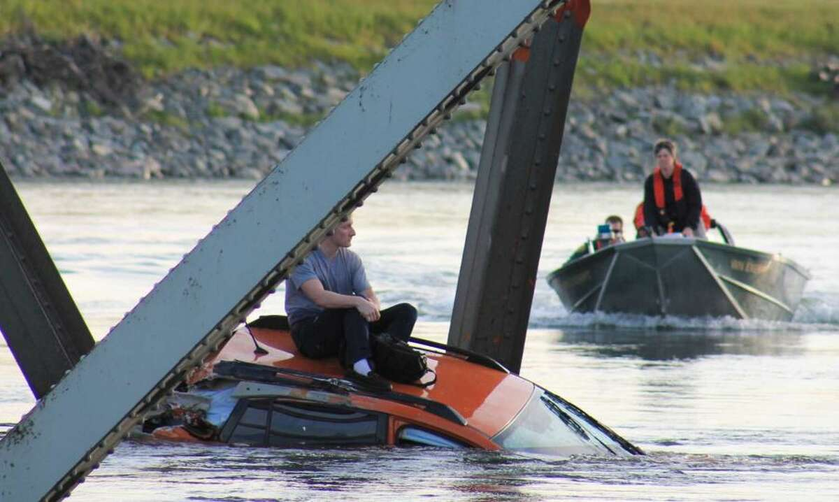 Two of the three victims to fall into the water, Bryce Kenning (L) and Dan Sligh (R), awaited rescue on top of their submerged cars.