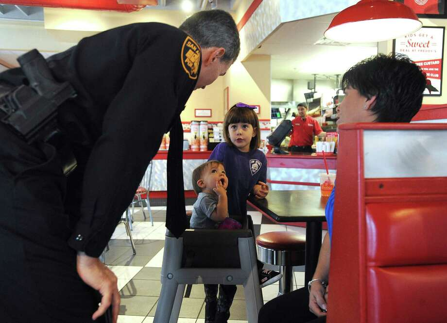 Police Chief William McManus of the San Antonio Police Department converses with Samantha , top, and Addison Grona as their mother, Rina, whose husband is a police sergeant, sits by at Freddy's Frozen Custard & Steak Burgers in The Rim on Friday Dec. 27, 2013. McManus was at Freddy's to thank owner-operator James Oberg and employees for a fundraising event for Officer Bobby Deckard, who died on December 20 after being shot as he pursued armed robbery suspects on December 8. Between 4 p.m. and 7 p.m. on Friday, 20 percent of all proceeds at Freddy's 10 San Antonio and New Braunfels area restaurants were slated for donation to the Deckard's family fund at Generations Federal Credit Union. Photo: Billy Calzada, San Antonio Express-News / San Antonio Express-News