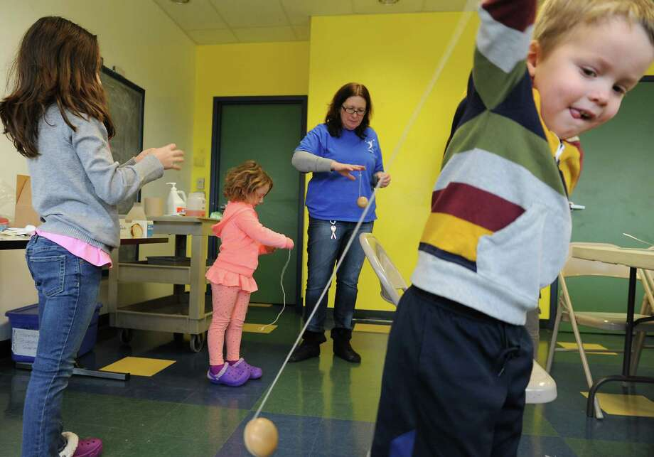 From left, Olivia Hopper, 8, her sister Natalie, 4, and Robbie Siebel, 5, right, all of Albany play with yo-yos as they learn the physics of toys from museum educator Dawn Baldwin, second from right, at the Children's Museum of Science and Technology on Friday, Dec. 27, 2013 in Troy, N.Y. (Lori Van Buren / Times Union) Photo: Lori Van Buren / 00025148A