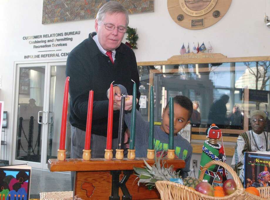Mayor David Martin and Christopher Smith (6) light a candle during the 19th annual Mayor's Kwanzaa Celebration at the Stamford Government Center on Friday  December 27, 2013. Photo: Dru Nadler / Stamford Advocate Freelance