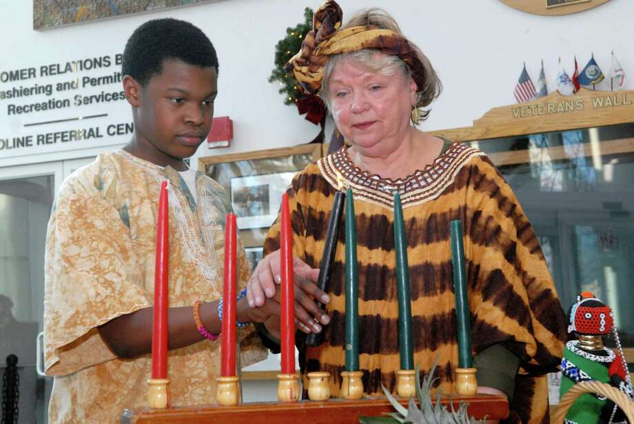 Cristian Colvin and Judith Rochon light a candle at the 19th annual Mayor's Kwanzaa Celebration at the Stamford Government Center on Friday  December 27, 2013. Photo: Dru Nadler / Stamford Advocate Freelance