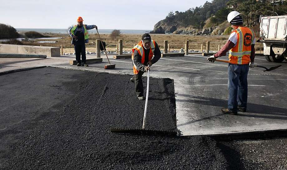 Antonia Morals spreads out asphalt as workers finish construction of the new parking lot at Muir Beach, which opens Saturday after a five-month-long closure. Photo: Lacy Atkins, The Chronicle