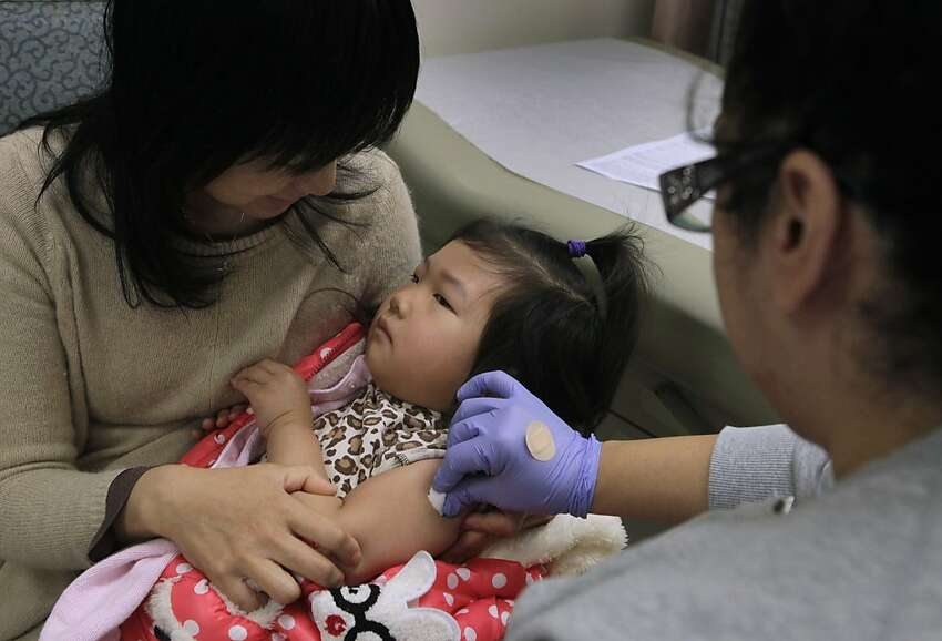 Meichen Wang comforts her 3-year-old daughter Mia Lin while nurse Alheli Hocker prepares Mia for a flu vaccination at the Kaiser Permanente injection clinic in Redwood City, Calif. on Friday, Dec. 27, 2013. A recent uptick in reported cases of influenza indicates the flu season is in full swing.