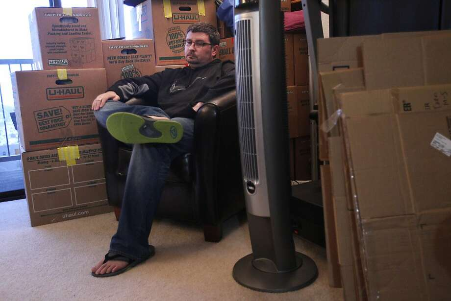 Todd Morgan discusses the difficult decision of moving out of the city while sitting in his living room surrounded by moving boxes December 18, 2013 at his and his wife's apartment in San Francisco, Calif. After four years in their apartment, the landlord decided to raise the rent by $200 and only gave 30 days notice. The two are moving to Alameda, where the cost of living is more affordable. Photo: Leah Millis, The Chronicle
