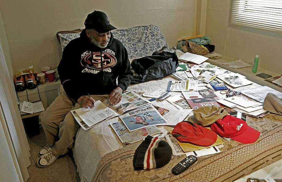Ronald Booker looks over his mail in his studio apartment in Visitacion Valley, where he moved after the fire. Season of Sharing covered the security deposit and bought the bed. Photo: Michael Macor, The Chronicle