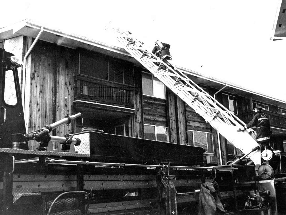Firefighters climb to the rook of the Candlelight Terrace condominium complex on Cold Spring Road, where a fire gutted a three-bedroom unit on Dec. 29, 1988.