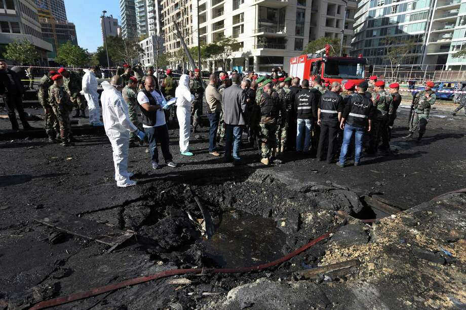 Lebanese army investigators in white coveralls examine a blast crater at the scene of car bomb in Beirut on Friday. The bomb killed Mohammed Chatah, a prominent pro-Western politician, and at least five others. Photo: Bilal Hussein, STF / AP