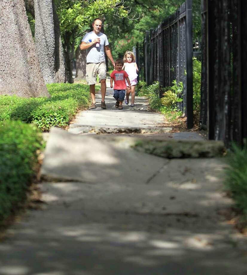 Daniel Spibey walks along the shoddy sidewalks with his children Hatty, 5, and Ned, 3, on Bayland Street in the Heights, Thursday, Aug. 8, 2013, in Houston.   ( Karen Warren / Houston Chronicle ) Photo: Karen Warren, Staff / © 2013 Houston Chronicle