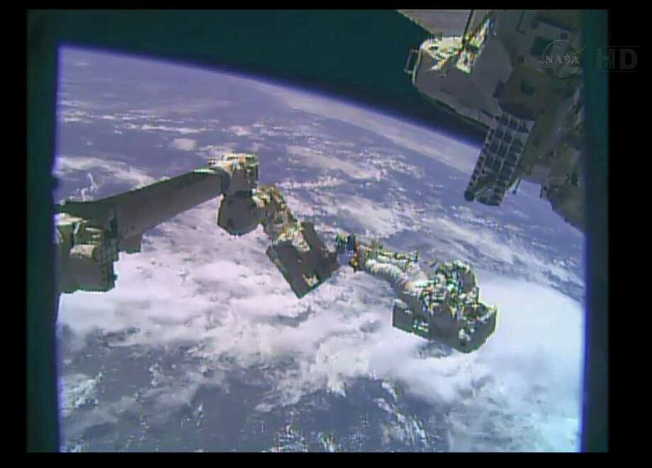 """This December 24, 2013 NASA TV still image shows  astronaut Mike Hopkins on the robotic arm during a spacewalk outside the Ineternational Space Station(ISS). Two NASA astronauts stepped out Tuesday on a rare Christmas Eve spacewalk to complete repairs at the International Space Station. """"The 10th spacewalk of the year at the International Space Station is now officially under way,"""" a NASA commentator said at 6:53 am (1153 GMT), as astronauts made a second outing to replace an ammonia pump module whose internal control valve failed December 11.The main task of the day is to retrieve a spare pump module from an external stowage platform and install it. NASA astronauts Rick Mastracchio, 53, and Mike Hopkins, 44, made swift work of their first spacewalk on Saturday, disconnecting and pulling out the old cooling pump that regulates the temperature of equipment at the orbiting space lab. AFP PHOTO / HO / NASA TV    == RESTRICTED TO EDITORIAL USE / MANDATORY CREDIT: """"AFP PHOTO / NASA TV   / NO SALES / NO MARKETING / NO ADVERTISING CAMPAIGNS / DISTRIBUTED AS A SERVICE TO CLIENTS ==HO/AFP/Getty Images Photo: HO, Handout / AFP"""