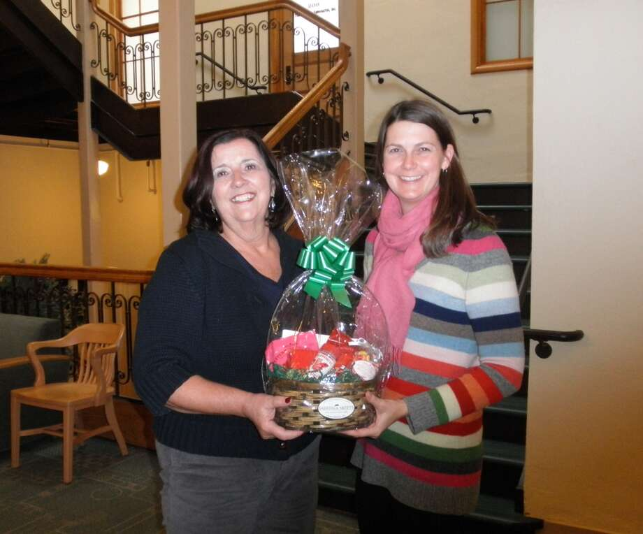 Noreen Nolan of Gansevoort, left, won a gift basket from Saratoga Sweets, which included a Peppermint Pig and other candies and confections, as part of the Saratoga Springs Preservation Foundation?s Candlelight House Tour earlier this month. With her is the foundation?s Samantha Bosshart. (Submitted photo)