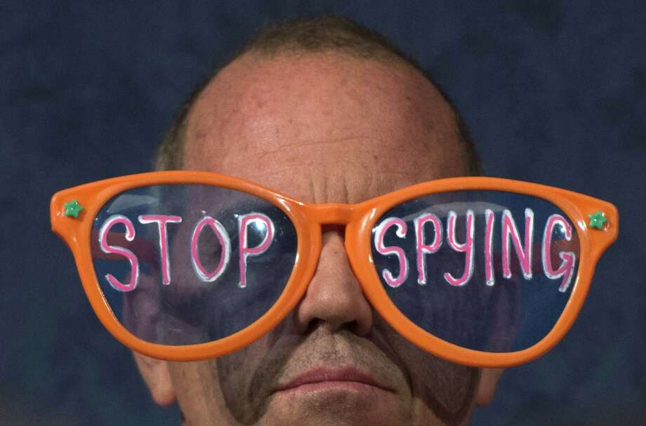 A protester with Code Pink wears giant glasses during a recent House committee hearing with testimony from National Security Agency Director Keith Alexander. Separate federal court rulings are divided on NSA domestic surveillance. Photo: JIM WATSON, Staff / AFP ImageForum