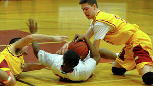 Moore Catholic's Wanjala Mwesiga, center, tries to fend off St. Joseph's Jonathan Dzurenda, left, and Connor Gallagher, as they try to steal the ball away, during Northeast 2013 Catholic Classic basketball tournament action in Stratford, Conn. on Friday December 27, 2013.