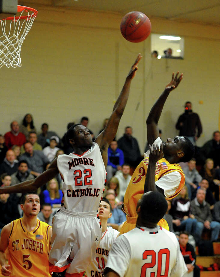 St. Joseph's Raekwon Reid releases a shot as Moore Catholic's Quadir Williams blocks, during Northeast 2013 Catholic Classic basketball tournament action in Stratford, Conn. on Friday December 27, 2013. Photo: Christian Abraham / Connecticut Post