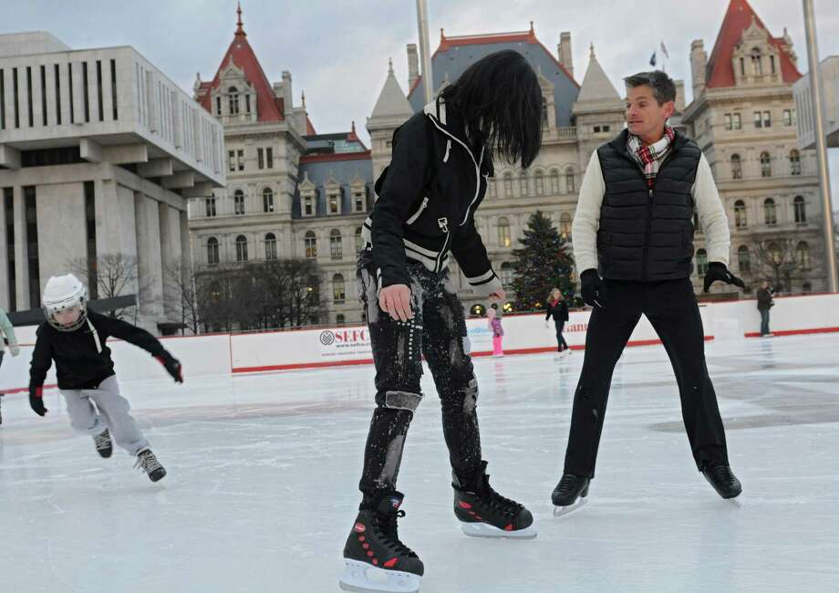 1992 Olympic silver medalist Paul Wylie, right, gives Raven Ward, 15, of Albany a few skating tips on the ice rink at the Empire State Plaza on Friday, Dec. 27, 2013 in Albany, N.Y. (Lori Van Buren / Times Union) Photo: Lori Van Buren / 00025116A