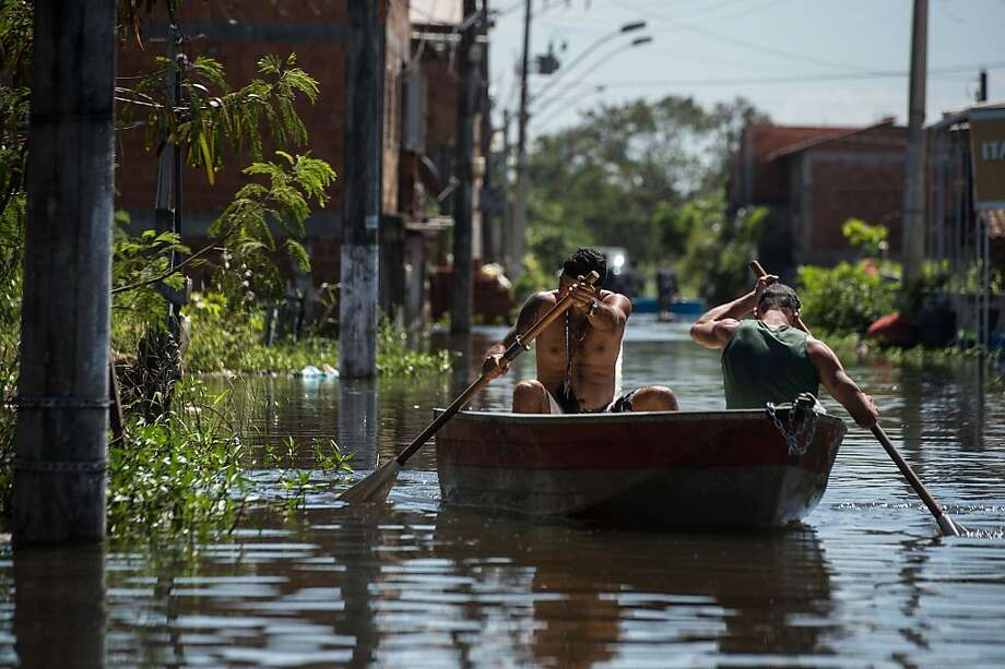 Men row on a boat along a flooded street in Vila Velha, Espirito Santo state, Brazil, on December 27, 2013. At least 44 people have died and more than 60,000 have been left homeless following torrential rains over the past few weeks in southeast Brazil.     TOPSHOTS/AFP PHOTO/YASUYOSHI CHIBAYASUYOSHI CHIBA/AFP/Getty Images Photo: Yasuyoshi Chiba, AFP/Getty Images