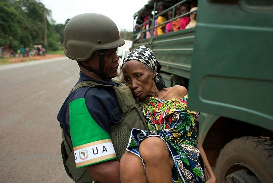 An African Union peacekeeper carries an elderly Cameroonian woman, too frail to walk, to a military vehicle shuttling Cameroonian citizens to the airport for an evacuation flight, in Bangui, Central African Republic, Friday, Dec. 27, 2013. Military escorts shuttled nationals of Chad and Cameroon to the airport Friday to board evacuation flights, as French troops stepped in to help Muslims fleeing north by road make it safely through hostile areas. (AP Photo/Rebecca Blackwell) Photo: Rebecca Blackwell, Associated Press
