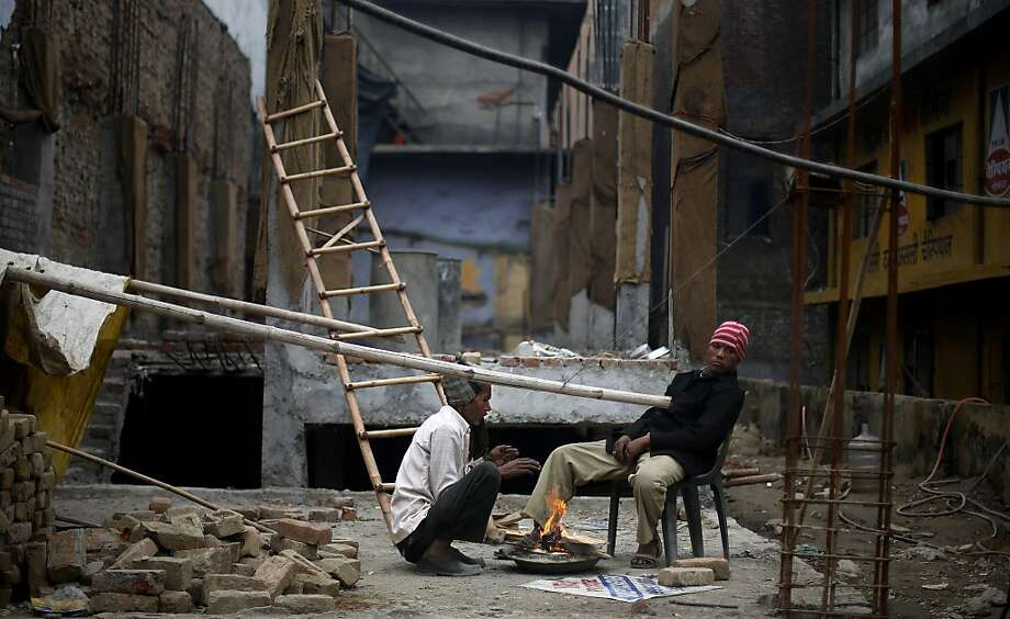 Indian laborers keep themselves warm near a small bonfire at an under construction building in New Delhi, India, Friday, Dec. 27, 2013. Large swathes of North India bore the brunt of cold wave and icy winds as temperature in several parts of the region breached the sub zero level, with Leh in Jammu and Kashmir witnessing the coldest day of the season, according to local news reports. (AP Photo/Altaf Qadri) Photo: Altaf Qadri, Associated Press