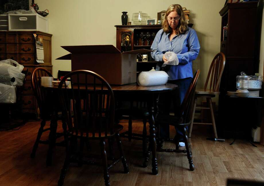 Leslie Lynch packs up belongings in her dining room in Glastonbury, Conn. Lynch, who lost her job last year, is moving out of her home of 21 years because she can no longer afford the mortgage payments. Photo: Jessica Hill, FRE / FR125654 AP