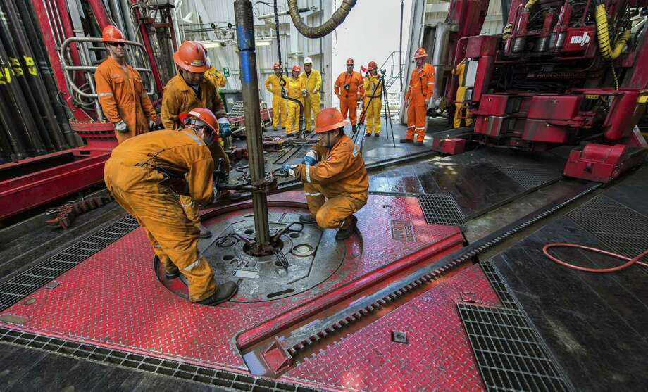 Derrick hands remove a drilling tool that has a sample of the seabed at La Muralla IV oil rig, which was working this summer for Mexico's state-owned company, Pemex, in the Gulf of Mexico. Photo: OMAR TORRES, Staff / AFP ImageForum