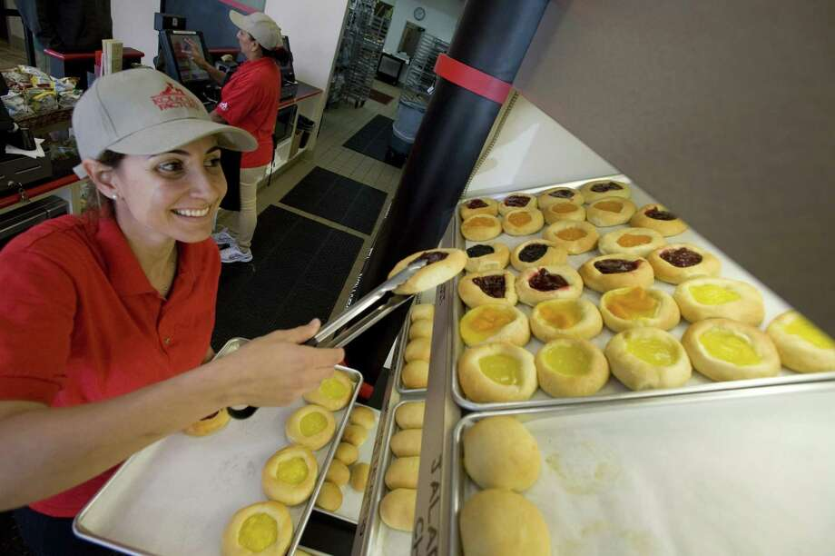 """Kolache Factory franchisee Kathy Skaff stocks the shelves of her shop in Tustin, Calif. Skaff opened a Kolache Factory after securing a $250,000 loan through the SBA Community Advantage program. """"I'm very lucky,"""" she says. Photo: Joshua Sudock, MBR / Orange County Register"""
