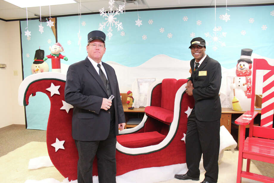 Staff members from the Lamar CISD transformed the administration building into scenes from 'The Polar Express' for visiting students from the Seguin Early Childhood Center. Playing the conductors are, from left, Walter Bevers and Bobby Holden. Photo: Lamar Consolidated Independent School District