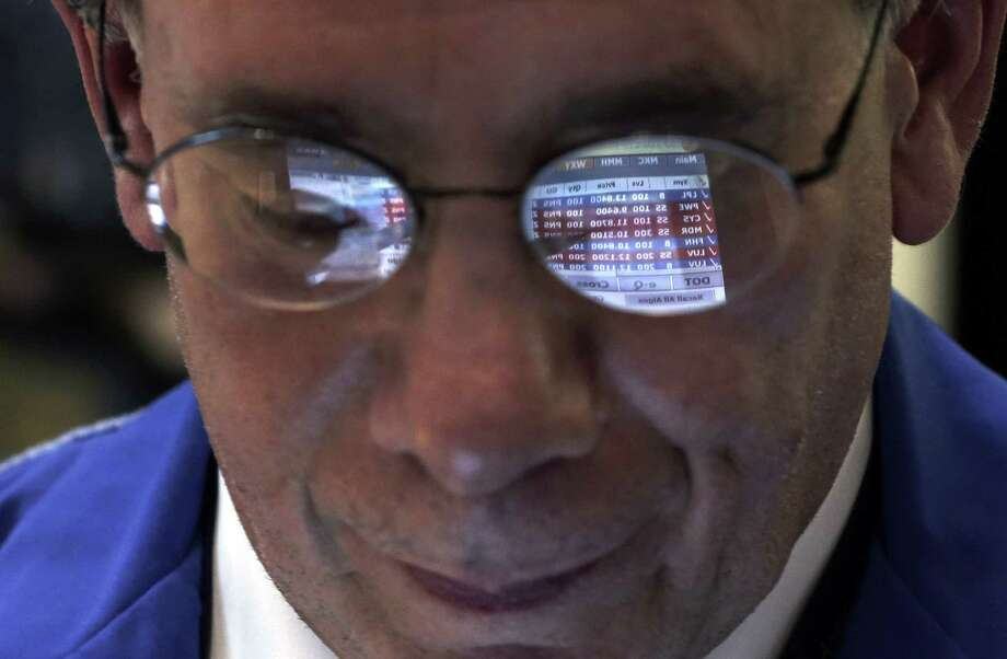 Trader Sal Suarino's glasses reflect the screen of his handheld device as he works on the floor of the New York Stock Exchange. Few market strategists believe that 2014 will be anywhere near as good as 2013. Photo: Richard Drew, STF / AP