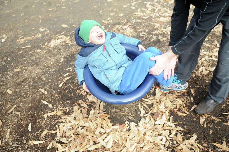 Eitan Rosen takes a turn on a spinning seat at the Bruce Park playground in Greenwich, Conn., Dec. 28, 2013. Photo: Keelin Daly / Stamford Advocate Freelance