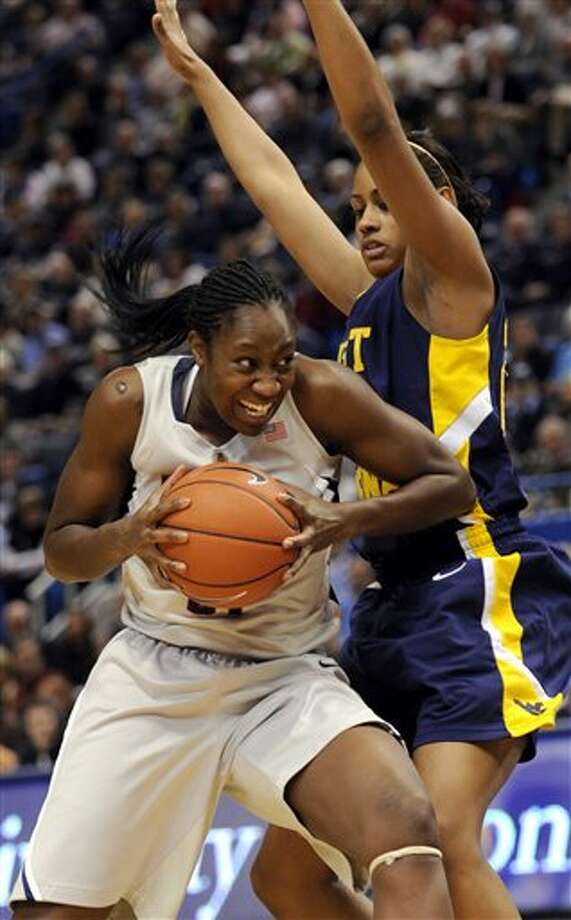 Connecticut's Tina Charles goes under West Virginia's Asya Bussie for a shot in the first half of an NCAA college basketball game in Hartford, Conn., Tuesday, Feb. 2, 2010. (AP Photo/Bob Child)