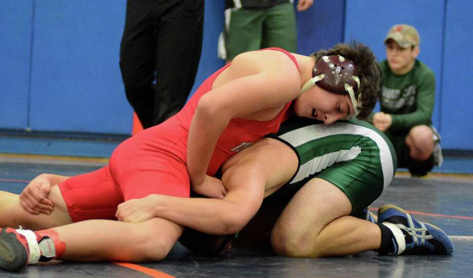 New Milfords John Ceconi, right, wrestles against Northwesterns Gabriel Schwartz  in the 160 lb weight catagory during the Danbury Holiday Wrestling Tournament at Danbury High School on Saturday Dec. 28, 2013. Photo: Lisa Weir / The News-Times Freelance