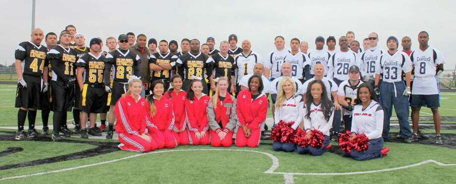 The Fort Bend County Sheriff's Office Enforcers and the Sugar Land Police Department Chargers recently played in their annual Holiday Bowl. The teams stand with the Travis High School cheerleaders and three Houston Texans Cheerleaders before the event. Photo: Fort Bend County Sheriff's Office