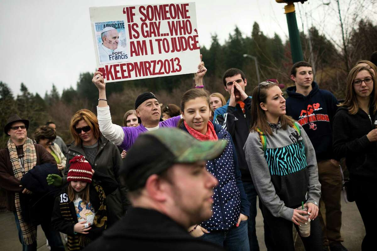 A crowd of nearly 30 students and supporters rallied for Eastside Catholic's former Vice Principal Mark Zmuda, who resigned his position after officials with the Archdiocese discovered that he was in a same-sex marriage and said he violated his contract Saturday, Dec. 28, 2013, outside of Eastside Catholic High School in Sammamish.