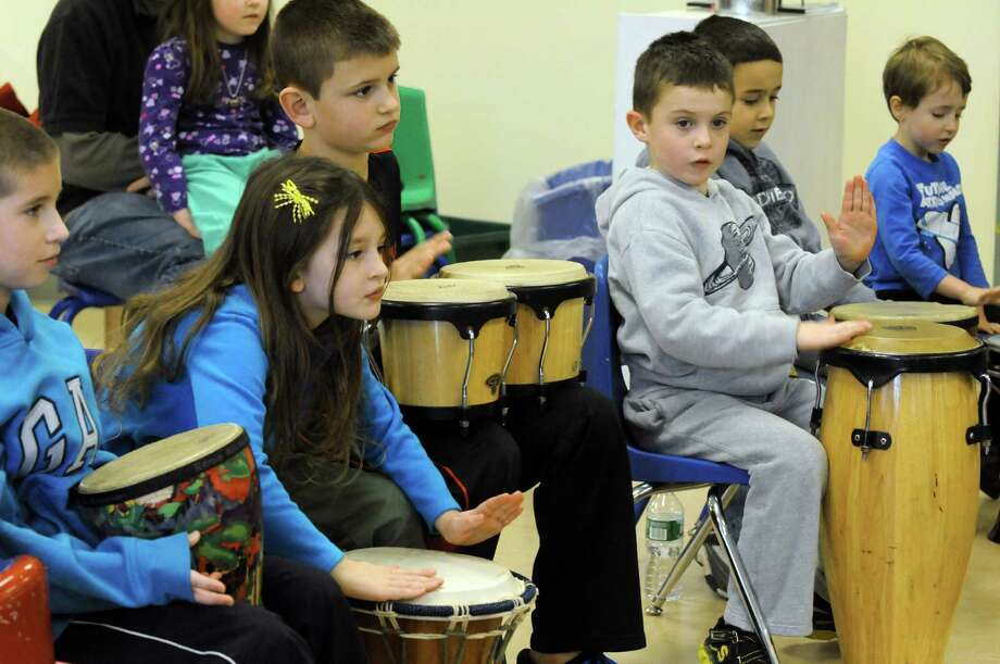 Child take part in an educational fundraiser, Leta€™s Drum for Food, taught by Jonathan Duda at the Woodland Hill Montessori School on Saturday Dec. 28, 2013 in North Greenbush, N.Y. Participants  hit an African djembe drum, crashed a Chinese gong, and heard the striking sound of a Brazilian cuica. A $5 donation per participant was requested or the equivalent in non-perishable food items. A collaboration of the Leta€™s Drum traveling music program and Rockya€™s Music Studio for kids 5 to 12 years, the event  benefited the Regional Food Bank of Northeastern NY. (Michael P. Farrell/Times Union) Photo: Michael P. Farrell / 00025136A