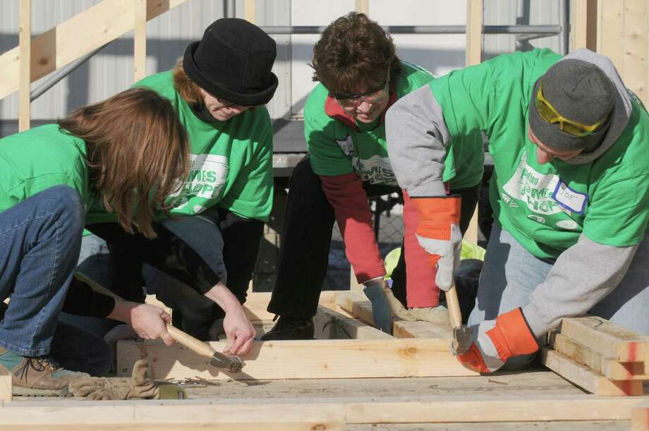 CDPHP employees, left to right, Maureen Gavin, Sheila Nelson, Lori Picard and Joe Beard build a home in with Habitat for Humanity Capital District on Saturday Dec. 28, 2013 in Albany, N.Y. The special a€œbuild daya€ marks the end of a year-long fundraising initiative in which CDPHP employees raised $40,000 for Habitat and Capital Region Sponsor-A-Scholar. The two organizations have partnered to provide homes and educational opportunities for local families. (Michael P. Farrell/Times Union) Photo: Michael P. Farrell / 00025178A