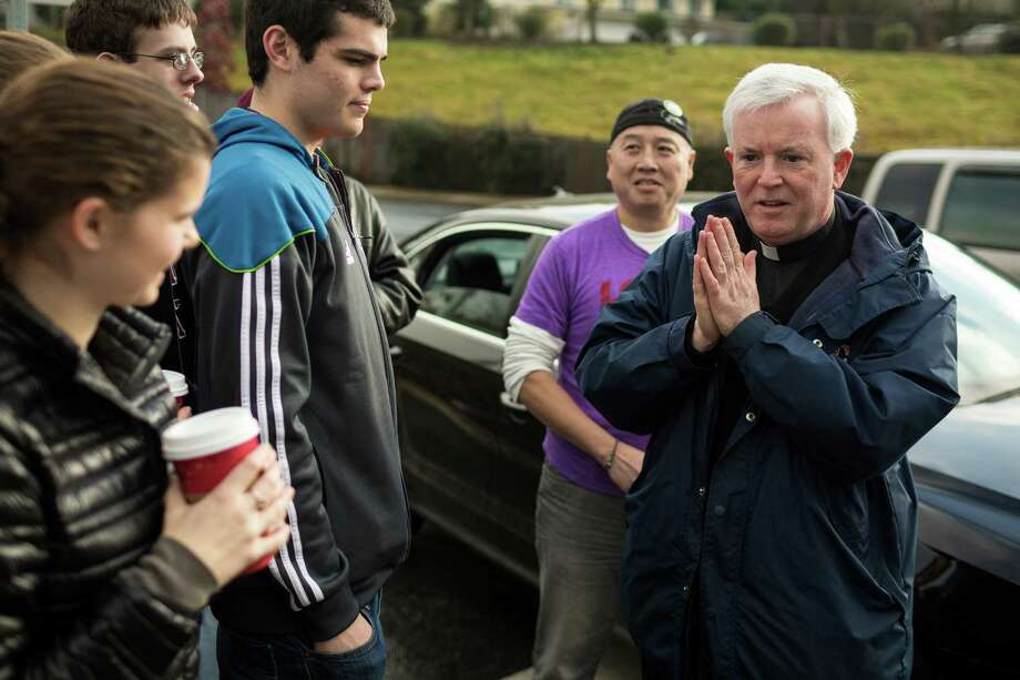 Father Bill Heric, right, chats with students and supporters during a rally for Eastside Catholic's former Vice Principal Mark Zmuda, who resigned his position after officials with the Archdiocese discovered that he was in a same-sex marriage and said he violated his contract Saturday, Dec. 28, 2013, outside of Eastside Catholic High School in Sammamish. While students said they believe Father Bill Heric is on their side, his contract with the school keeps the on-site priest unable to publicly speak out. Photo: JORDAN STEAD, SEATTLEPI.COM / SEATTLEPI.COM