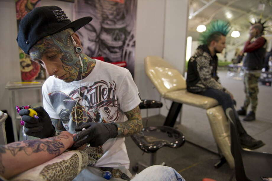 D. tattoo technicians Photo: EITAN ABRAMOVICH, Andrew Merrill / 2013 AFP