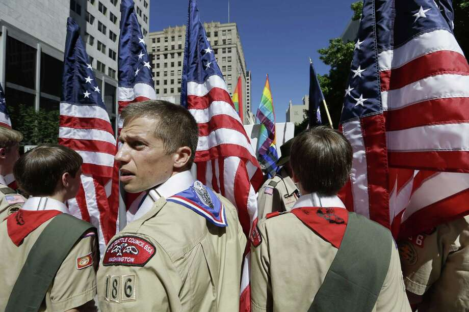 FILE - In this June 30, 2013 file photo, Boy Scouts from the Chief Seattle Council carry U.S. flags as they prepare to march in the Gay Pride Parade in downtown Seattle. The Boy Scouts of America, in the most contentious change of membership policy in a 103-year history, will accept openly gay youths in Scout units starting on New Year's Day 2014. (AP Photo/Elaine Thompson, File) Photo: Elaine Thompson, STF / AP